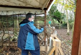 person working a green pole lathe
