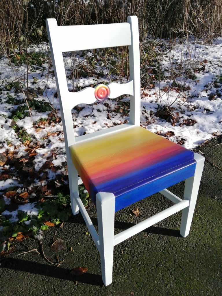 individual chair painted white and the seat has colourful rainbow stripes