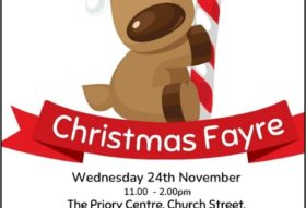 a poster for a christmas fayre event being held at The Priory Centre Leominster on 24th November 2021. The image shows a cartoon style dog reindeer character holding a red and whit candy cane sitting on a red ribbon banner.